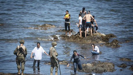 Spanish soldiers stand guard and intervene as migrants arrived swimming to Spanish territory of Ceuta on May 18, 2021.