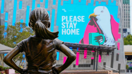 """The Fearless Girl Statue looks at a """"Please Stay Home"""" sign in an empty Federation Square on the first day of a five-day lockdown implemented in the state of Victoria in response to the coronavirus disease (Covid-19) outbreak in Melbourne, Australia, (FILE PHOTO) © REUTERS/Sandra Sanders/"""