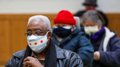A Chicago resident wearing a face mask in the colors of the city's flag waits to get the Covid-19 vaccine in this February 13, 2021 file photo.