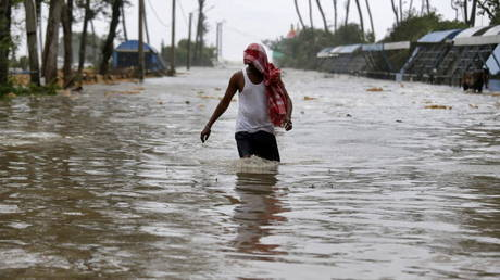 A man wades through a water-logged road after rains ahead of Cyclone Yaas at Digha in Purba Medinipur district in the eastern state of West Bengal, India, May 26, 2021 © REUTERS/Rupak De Chowdhuri
