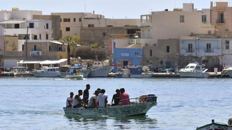 FILE PHOTO. Migrants arrive on a boat in the Italian Pelagie Island of Lampedusa.