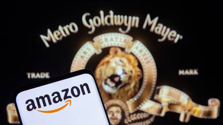 A smartphone with the Amazon logo is seen in front of a displayed MGM logo in this illustration taken May 26, 2021 © Reuters / Dado Ruvic