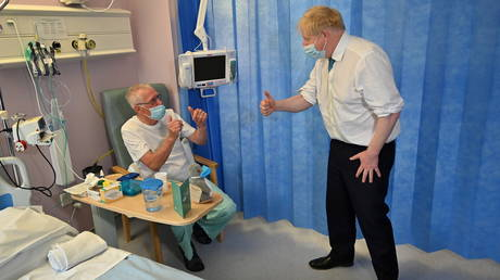 Britain's PM Boris Johnson speaks with a patient as he visits Colchester hospital in Britain on May 27, 2021.