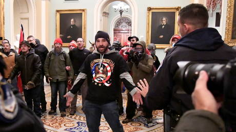 A supporter of President Donald Trump wearing a QAnon shirt confronts police at the US Capitol in Washington DC, January 6, 2021 © Reuters / Mike Theiler