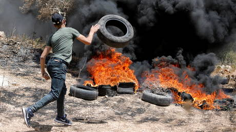 A Palestinian demonstrator throws a tire onto a fire during a protest against Israeli settlements in the occupied West Bank. © Reuters / Raneen Sawafta