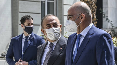 Turkish Foreign Minister Mevlut Cavusoglu (C) and Greek Foreign Minister Nikos Dendias (R) in Athens, Greece, May 31, 2021. © Aris Messinis/AFP