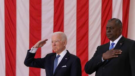 U.S. President Joe Biden salutes next to U.S. Secretary of Defense Lloyd Austin during a National Memorial Day ceremony at Arlington National Cemetery in Arlington, Virginia