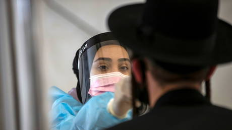 FILE PHOTO: A healthcare worker takes a swab sample from an Ultra-Orthodox Jewish man for the coronavirus disease (COVID-19) test, after returning from overseas, at Ben Gurion International Airport in Lod, near Tel Aviv, Israel April 13, 2021.© REUTERS/Ronen Zvulun