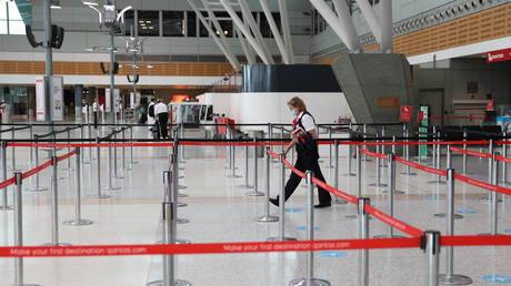 A person walks through a terminal at Sydney Airport in Sydney, Australia, December 2020. © Loren Elliott / Reuters