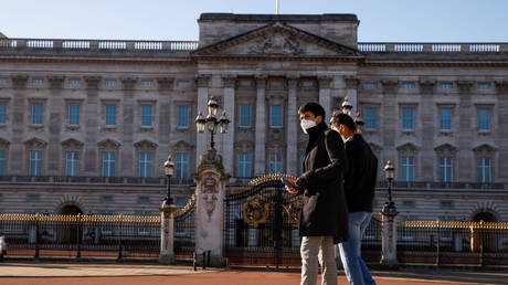 People wearing face masks walk past Buckingham Palace amid the coronavirus disease (COVID-19). © REUTERS / John Sibley