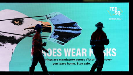 FILE PHOTO: Workers walk past a 'Heroes Wear Masks' sign on the first day of a seven-day statewide lockdown, in Melbourne, Australia, May 28, 2021.