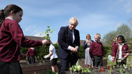 Britain's Prime Minister Boris Johnson helps out in the vegetable garden as he visits Cleves Cross Primary School, in Ferryhill, Britain (FILE PHOTO) © Scott Heppell/Pool via REUTERS