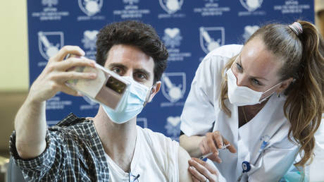 A medical staff member takes a photo as he is vaccinated by a medical worker against Coronavirus disease(COVID-19) at Tel Aviv Sourasky Medical Center as Israel starts the COVID 19 vaccination campaign on December 20, 2020 in Tel Aviv, Israel. © Amir Levy/Getty Images