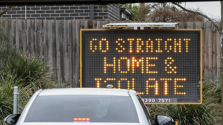 A sign reading 'Go straight home and Isolate' is seen at the exit of a drive through covid-19 testing site at Highpoint shopping centre on July 04, 2020 in Melbourne, Australia. © Asanka Ratnayake/Getty Images