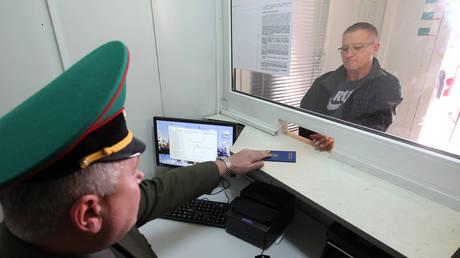 An employee of the Belarusian Border Service checks passports at the Kozlovichi checkpoint in the Brest Region. © Sputnik / Andrei Aleksandrov