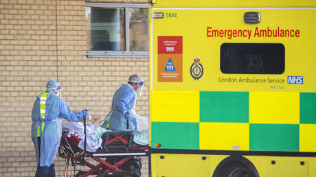 NHS workers in PPE take a patient with an unknown condition to an ambulance at Queens Hospital on April 21, 2020 in London, England. © Justin Setterfield/Getty Images
