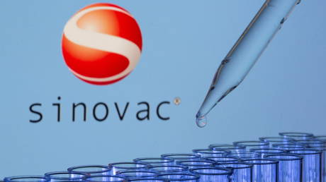 Test tubes are seen in front of a displayed Sinovac logo in this illustration taken, May 21, 2021. © REUTERS/Dado Ruvic