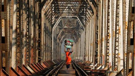 Woman carrying luggage walks along a railway track on the outskirts of Mumbai. © Reuters / Francis Mascarenhas