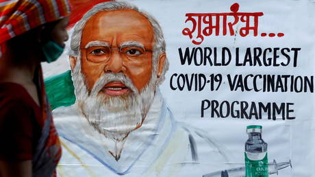 A woman walks past a painting of Indian Prime Minister Narendra Modi a day before the inauguration of the COVID-19 vaccination drive, on a street in Mumbai, India, (FILE PHOTO) © REUTERS/Francis Mascarenhas