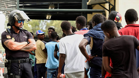 FILE PHOTO. African immigrants wait in a row as they enter the immigrant center CETI in the Spanish enclave Ceuta, after some 200 refugees crossed the border fence between Morocco and Ceuta. © Reuters / Fabian Bimmer