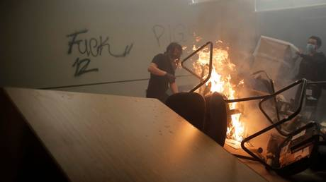 Rioters are shown inside a Minneapolis police station after setting fire to its entrance in May 2020.