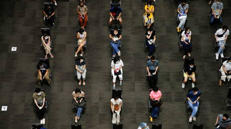 People wait to receive the first dose of the AstraZeneca Covid-19 vaccine against the coronavirus disease as Thailand start a mass inoculation at a gymnasium inside the Siam paragon Shopping center, Bangkok, Thailand June 7, 2021 © REUTERS/Soe Zeya Tun