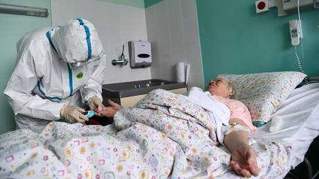 The doctor works with the patient in the ward of the hospital for patients with coronavirus infection COVID-19 on the basis of the City Clinical Hospital No. 67 in Moscow. © Sputnik / Alexey Maishev