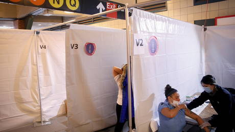 Commuter receives Johnson & Johnson vaccine at a subway station in the Brooklyn borough of New York City
