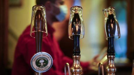 Empty pint glasses sit on the top of beer pumps of the Peveril Of The Peak pub signifying they have been disconnected from the barrels ahead of new Tier-3 Covid-19 restrictions on October 22, 2020 in Manchester, England. © Christopher Furlong/Getty Images