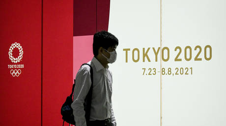 A man walks past a Tokyo 2020 advertising poster at the Shinjuku Metro Station, in Shinjuku area of Tokyo. © Cezary Kowalski/SOPA Images/LightRocket via Getty Images