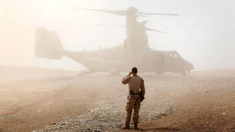 FILE PHOTO: A US Marine watches as an Osprey aircraft lands at Forward Operating Base Shukvani, Afghanistan.