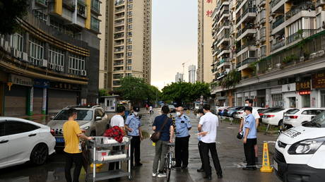 Police officers speak to people behind a police line near a residential area where only entering is allowed, following new cases of the coronavirus disease (Covid-19), in Guangzhou's Liwan district, Guangdong province, China May 29, (FILE PHOTO) © . cnsphoto via REUTERS