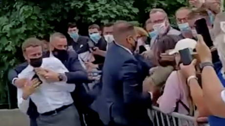 French President Emmanuel Macron is protected by a security member after getting slapped by a member of the public during a visit in Tain-L'Hermitage, France, in this still image taken from video on June 8, 2021. © BFMTV/ReutersTV via REUTERS