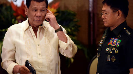 President Rodrigo Duterte holds a caliber 45 pistol while Eduardo Ano, a Chief of the Armed Forces of the Philippines (AFP), looks on during a turnover ceremony for procured firearms for the AFP at the Malacanang presidential palace in metro Manila, Philippines (FILE PHOTO) © REUTERS/Dondi Tawatao