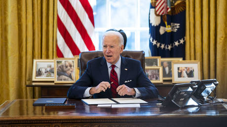 US President Joe Biden signs executive actions in the Oval Office of the White House on January 28, 2021 in Washington, DC. © Doug Mills-Pool/Getty Images