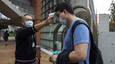 Taiwanese students get their temperature checked as they enter the Taipei American school on March 18, 2020 in Taipei, Taiwan. © Paula Bronstein/Getty Images