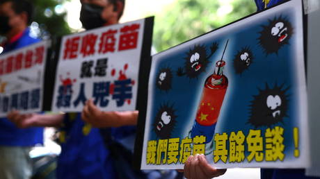 FILE PHOTO. People hold placards calling for Taiwan government to allow the use of Chinese-made Covid-19 vaccines in Taipei, Taiwan.