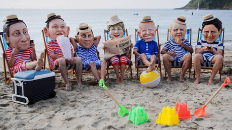 Oxfam activists wearing papier mache heads depicting G7 leaders perform during a protest at Swanpool Beach near Falmouth, during the G7 summit, in Cornwall, Britain, June 12, 2021. © Reuters / Phil Noble.