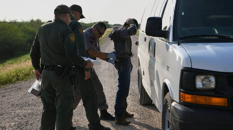 FILE PHOTO: An undocumented migrant is searched at a transport van after being apprehended by US Border Patrol agents following an illegal crossing of the Rio Grande near Penitas, Texas. © Reuters / Loren Elliott.