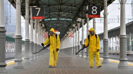 Russian Emergencies Ministry workers in protective gear disinfect a platform of the Belorussky railway station amid the coronavirus outbreak in Moscow. © Sputnik / Pavel Bednyakov.
