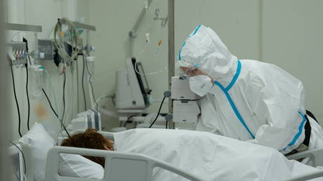 FILE PHOTO: A medical worker takes care of a patient at a temporary hospital in the Krylatskoye Ice Palace, where patients suffering from the coronavirus disease (COVID-19) are treated, in Moscow, Russia June 11, 2021. © Denis Grishkin/Moscow News Agency/Handout via REUTERS