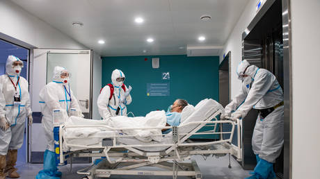 Medical specialists wearing protective gear transport a patient at the City Hospital Number 40, where patients suffering from the coronavirus disease are treated, in Kommunarka settlement in the south of Moscow, Russia.