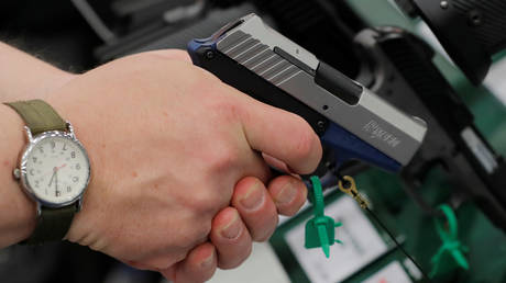 FILE PHOTO: A man holds a Remington handgun during the annual National Rifle Association (NRA) convention in Dallas, Texas.