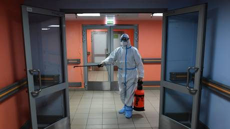 An employee wearing personal protective equipment (PPE) disinfects the corridor in the intensive care unit of the City Clinical Hospital No 67, where patients suffering from the coronavirus disease are treated, in Moscow, Russia.
