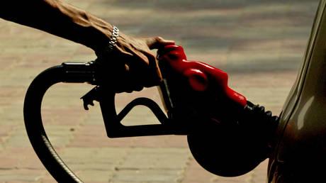 Indian worker fills a car at a petrol pump in New Delhi