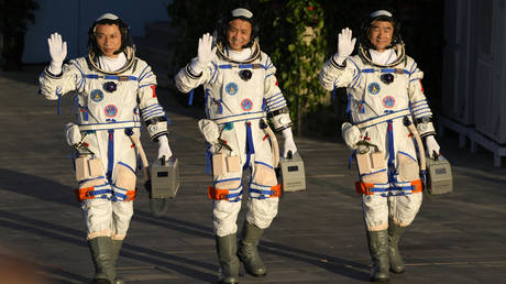 Chinese astronauts, from left, Tang Hongbo, Nie Haisheng, and Liu Boming before liftoff in northwestern China, Thursday, June 17, 2021