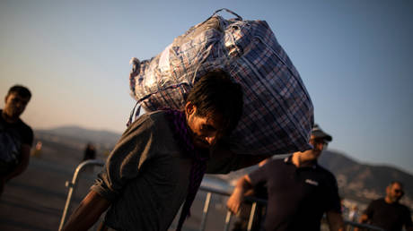 FILE PHOTO. A migrant from Afghanistan carries his belongings as he waits to board a catamaran that will transfer refugees and migrants to the mainland, in Mytilene on the island of Lesbos, Greece. © Reuters / Alkis Konstantinidis.