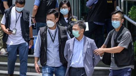 Apple Daily Chief Operations Officer Chow Tat Kuen (2nd R) escorted by police from offices of Apple Daily newspaper in Hong Kong on June 17, 2021