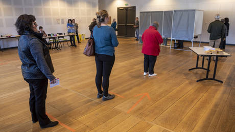 Voters stand on markers to keep them at least one metre apart prepare to cast their ballot in a polling station in Sare, France. © Gari Garaialde/Getty Images