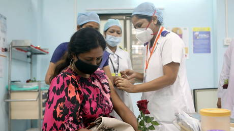 FILE PHOTO: A healthcare worker holding a rose receives an AstraZeneca's COVISHIELD vaccine, during the coronavirus disease (COVID-19) vaccination campaign, at a medical centre in Mumbai, India, January 16, 2021. © REUTERS/Francis Mascarenhas
